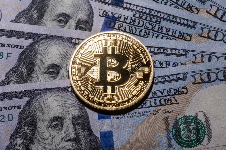 un bitcoin posé sur des billets de dollars